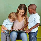 Children and kindergarten teacher reading together in a book