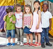 Many interracial children standing together in a kindergarten group