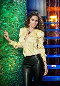 foto of blouse  - Attractive brunette woman with long hair in elegant yellow blouse and black leather pants standing near bright green wall in a nightclub - JPG