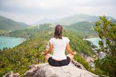 stock photo of samadhi  - Yoga meditation in lotus pose by woman on the peak of mountain - JPG