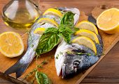 Dorado fish with lemon and spices on a wooden board