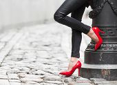 stock photo of black pants  - Woman wearing black leather pants and red high heel shoes in old town - JPG