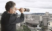 Business concept.  Business man looks through a telescope