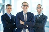 Three confident business workers smiling at camera