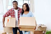 pic of love-making  - young black african couple moving boxes into new home together making a successful life - JPG