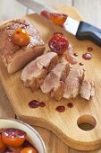 stock photo of duck breast  - Roasted duck breast in citrus sauce on wooden board