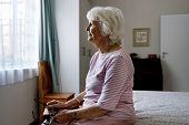 foto of solemn  - A solemn elderly woman sitting on her bed dealing with depression - JPG