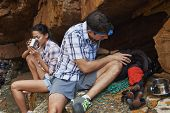A hiking couple taking a break by a cave with their hiking utensils around them