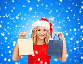 sale, gifts, christmas, holidays and people concept - smiling woman in red dress and santa helper hat with shopping bags over blue snowing background