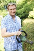 picture of electric trimmer  - Man Cutting Garden Hedge With Electric Trimmer