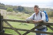 Senior Man Hiking In Countryside Resting By Gate