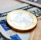 one euro coin on a banknote of hundred dollars