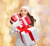 happiness, winter holidays, christmas and people concept - smiling young woman in santa helper hat with gifts over beige lights background