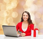 christmas, holidays, technology and shopping concept - smiling woman with credit card, gift box and laptop computer over beige lights background