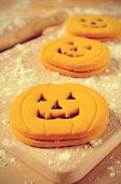 some cookies in the shape of jack-o-lanterns on a table sprinkled with wheat flour
