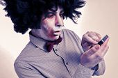 hipster zombie with an afro using a smartphone, with a filter effect