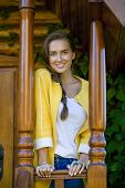 Beautiful young woman standing on the porch of a wooden house