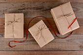 High angle shot of three plain wrapped Christmas presents. Brown paper and twine wrapped packages with a red ribbon running through the middle on rustic wood surface.