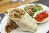 stock photo of curry chicken  - Chicken curry roti wrap with salad and relish - JPG