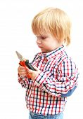 Little boy examines pliers.