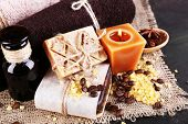 Organic soap with coffee beans, sea salt on wicker mat, on  table, on dark background, Coffee spa concept