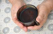 Old Hands Holding Cap Of Tea