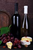 Wine in bottles, Camembert and brie cheese, grapes and wooden barrel on wooden table on wooden background