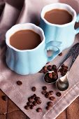Cups of coffee with napkin on wooden table