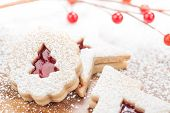 pic of linzer  - Christmas Tree Linzer cookie with powdered icing sugar and red decorations in the background - JPG