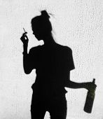 picture of teen smoking  - Shadow of sad girl with cigarette and bottle of wine smoking around on wall background  - JPG