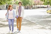 Full length of young male and female college students walking on footpath