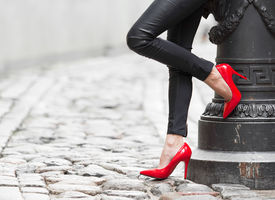 picture of erotic  - Woman wearing black leather pants and red high heel shoes in old town - JPG