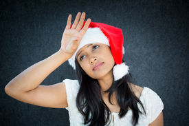 stock photo of spoiled brat  - Closeup portrait of annoyed woman in Santa Claus hat hand on forehead playing tragedy expressing holiday stress isolated on grey background - JPG