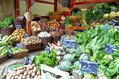image of stall  - Variety of root green vegetables in baskets with price tags on a market stall - JPG