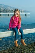 pic of pier a lake  - Portrait of a cute little caucasian girl sitting on a pier on Lake Geneva with the Lavaux in the backround - JPG
