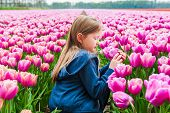 Cute little girl playing with tulips on a nice spring day