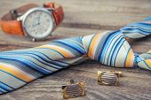 Tie, cufflinks and watches on the old wood background