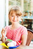 Cute little girl eating ice cream, outdoor portrait