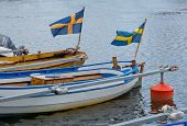 Two boats with waving Swedish flags