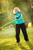 image of 70-year-old  - 70 years old Senior Woman doing Exercises with the Plastic Hoop at the Green Meadow in the Bright Autumn Evening - JPG