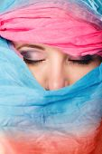 stock photo of burka  - Young woman makeup on eyes hiden her face with multicolored shawl blue background - JPG