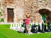 Cute toddler boy playing huge chess outside on a nice sunny day