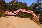 foto of track-hoe  - Large track hoe excavator working on large dirt pile on a new commercial development construction project - JPG