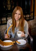 stock photo of churros  - young beautiful American student tourist girl sitting having spanish typical breakfast hot chocolate with churros smiling happy in tourism and holidays travel in Europe concept - JPG