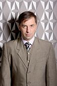Serious Business Man Standing Near The Wall - Stock Photo
