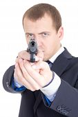 Serious Man In Business Suit Aiming Gun At Camera Isolated On White