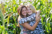 Smiling friends embracing at corn field background