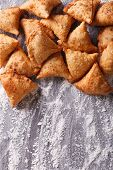 picture of samosa  - A pile of baking samosas on a floured table - JPG