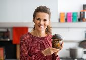 Portrait Of Happy Young Housewife Showing Jar Of Pickled Mushroo