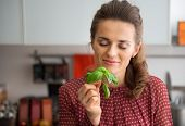Young Housewife Enjoying Fresh Basil